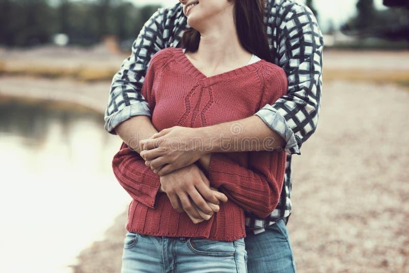 Lyckliga unga par som tycker om på stranden royaltyfri fotografi