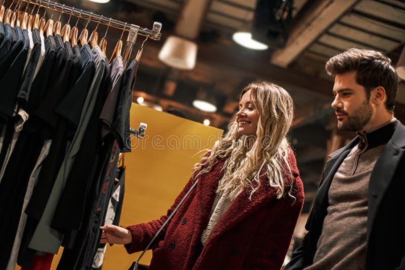 Lyckliga unga par som väljer den handgjorda klänningen på den lilla gatamarknaden fotografering för bildbyråer