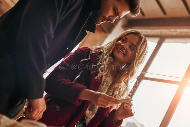 Lyckliga unga par som väljer handgjorda cristmasgarneringar Kantjusterat foto royaltyfri bild