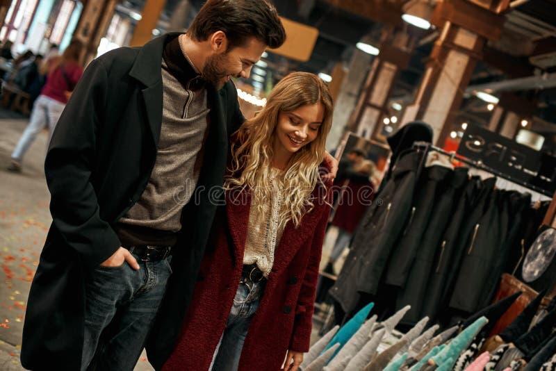 Lyckliga unga par talar på den lilla gatamarknaden, medan välja kläder royaltyfria foton