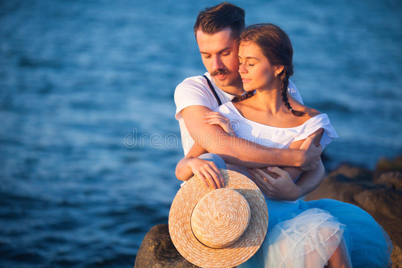 Lyckliga unga romantiska par som kopplar av på stranden som håller ögonen på solnedgången royaltyfria bilder