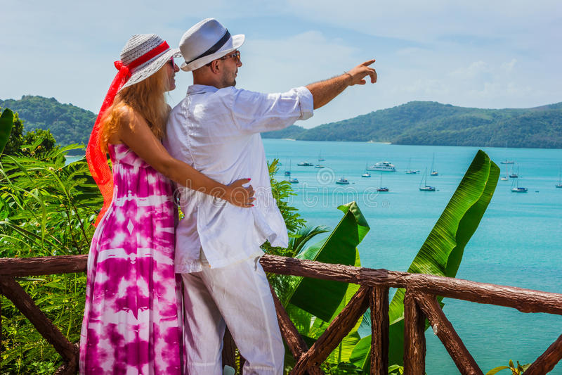 Lyckliga unga romantiska par som ser tillsammans till havet royaltyfria bilder
