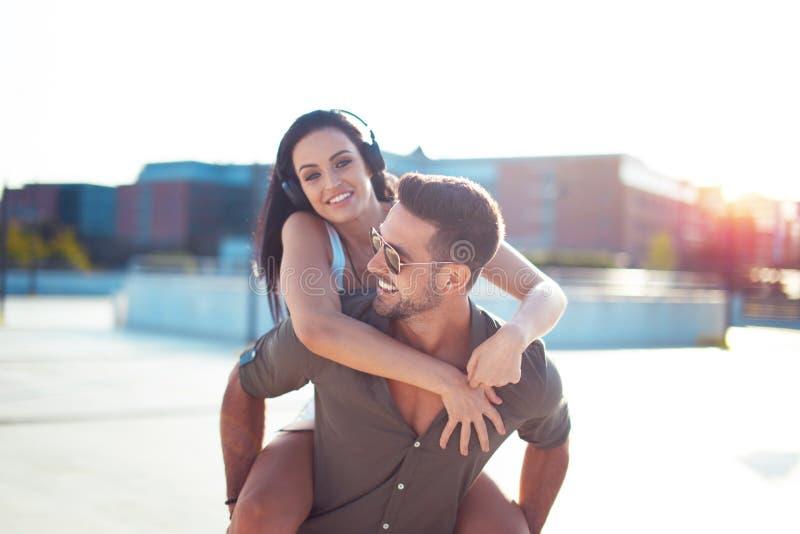 Lyckliga unga stads- par har gyckel i stadsridning på ryggen royaltyfri bild