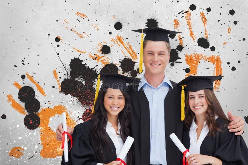 Lyckliga unga studenter som rymmer diplom mot grå färger, guling och svart, plaskade bakgrund arkivbild