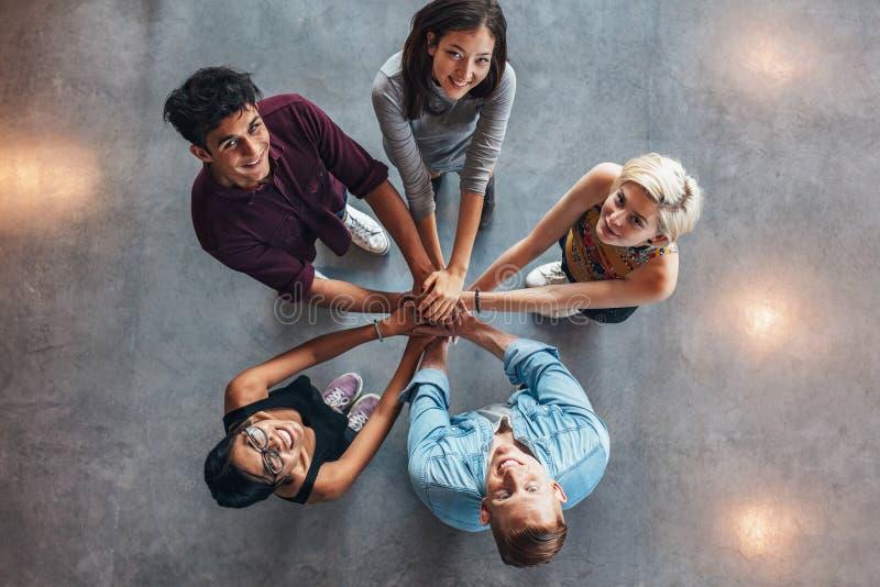 Lyckliga unga studenter som visar enhet arkivbild