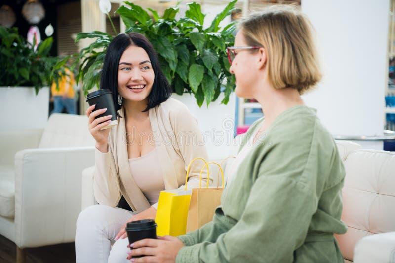 Lyckliga unga trendiga kvinnor som tar ett kaffeavbrott, når att ha shoppat och att le med engå i deras händer mot royaltyfri fotografi
