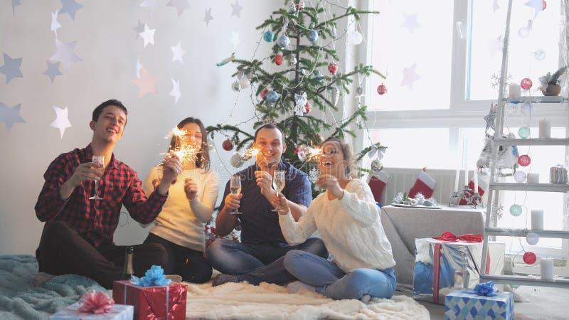 Lyckliga unga vänner dricker champagne och bränner tomtebloss under firar nytt år eller julafton royaltyfri foto