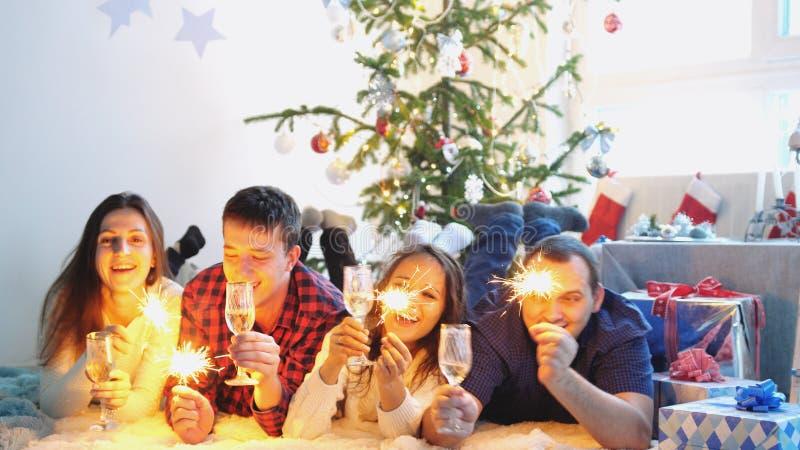 Lyckliga unga vänner dricker champagne och bränner tomtebloss under firar nytt år eller julafton och att ha stor tid royaltyfri bild
