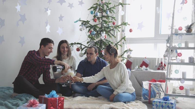 Lyckliga unga vänner häller champagne under firar nytt år eller julafton och att ha stor tid, i att koppla av hemmet arkivbilder