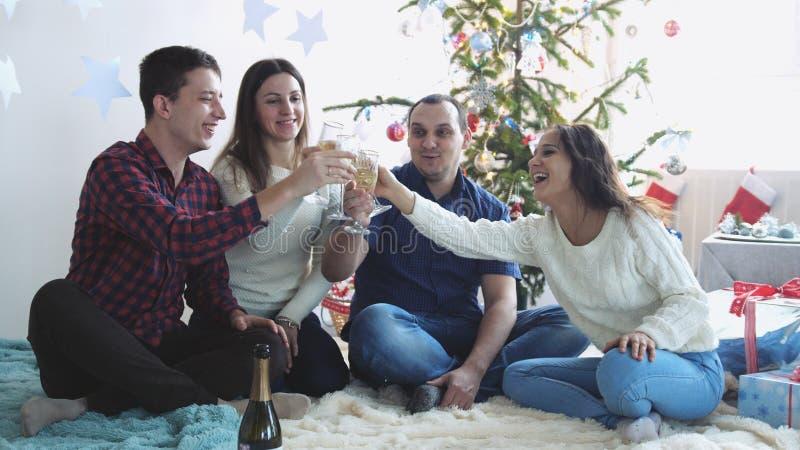 Lyckliga unga vänner klirrar exponeringsglas av champagne under firar nytt år eller julafton och att ha stor tid, i att koppla av fotografering för bildbyråer