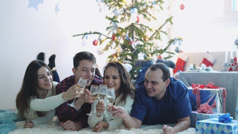 Lyckliga unga vänner ligger på ett filtfinkaexponeringsglas av champagne under firar nytt år eller julafton och att ha stor tid royaltyfria bilder