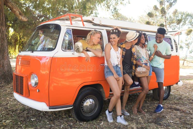 Lyckliga unga vänner på fält på campingplatsen royaltyfri bild