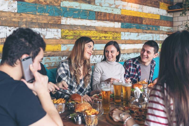 Lyckliga unga vänner som firar med pizzahamburgare och dricker öl på stångrestaurangen arkivfoton