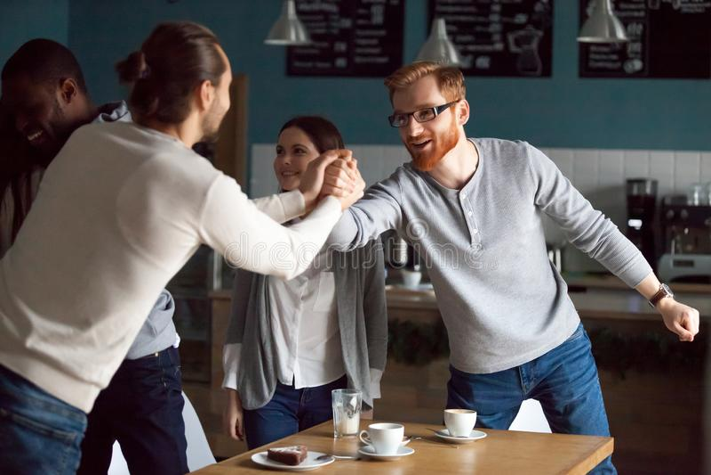 Lyckliga unga vänner som hälsar på det vänliga mötet i kafé arkivfoto