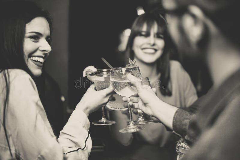 Lyckliga unga vänner som rostar och hurrar coctailar på diskostången - blandras- folk som har gyckel som tycker om drinkar på klu fotografering för bildbyråer