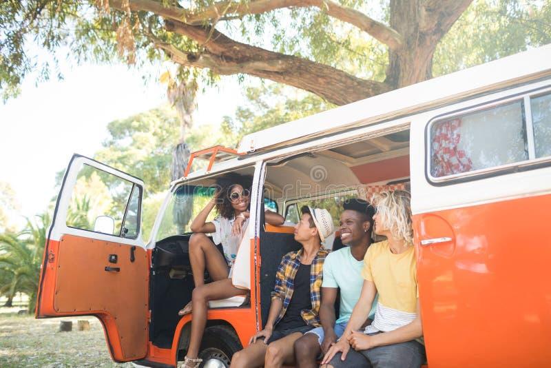 Lyckliga unga vänner som sitter i campareskåpbil arkivfoton