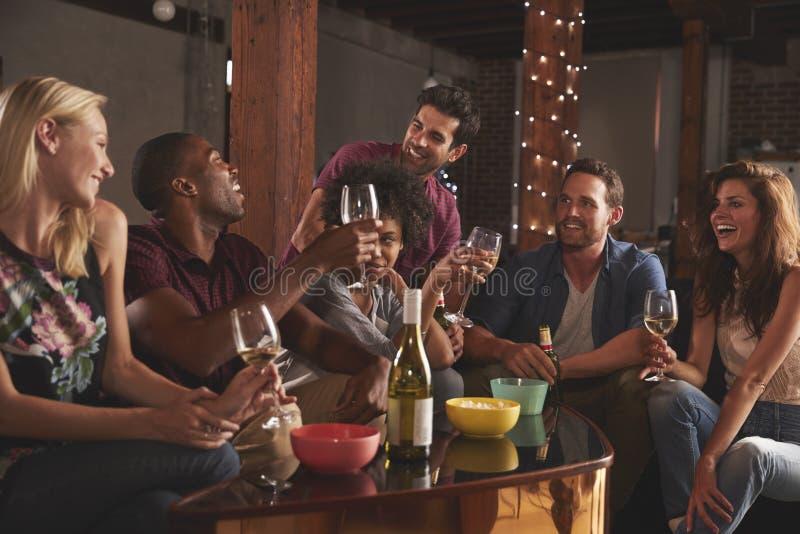 Lyckliga unga vuxen människavänner som har ett parti hemma royaltyfri bild