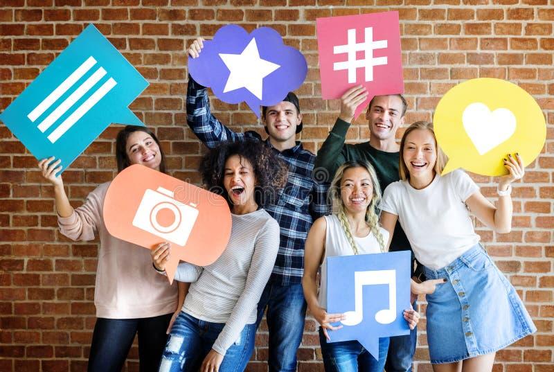 Lyckliga unga vuxna människor som rymmer tanke, bubblar med sociala massmediabegreppssymboler arkivbild