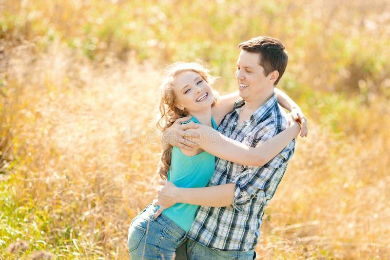 Lyckliga unga vuxna par som är förälskade på fältet Två, man och wom royaltyfria bilder