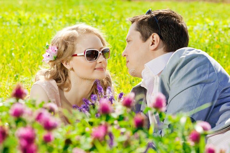 Lyckliga unga vuxna par som är förälskade på fältet Två, man och wom royaltyfri fotografi