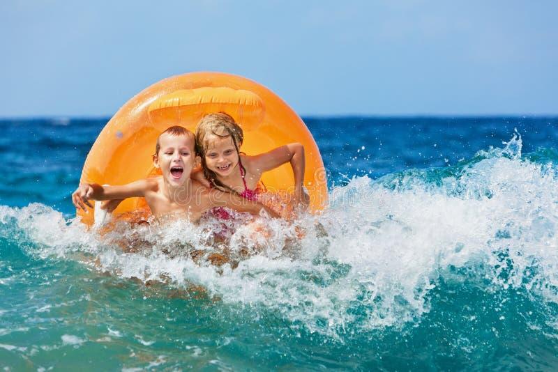 Lyckliga ungar har gyckel i havsbränning på stranden arkivfoto