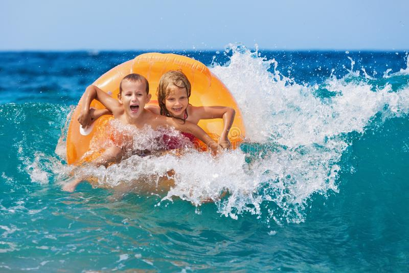 Lyckliga ungar har gyckel i havsbränning på stranden fotografering för bildbyråer