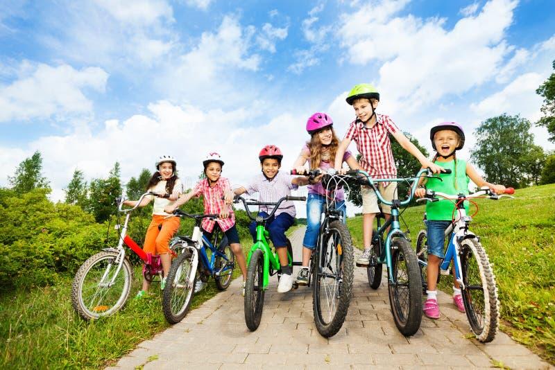Lyckliga ungar i rad bär färgrika cykelhjälmar arkivfoto