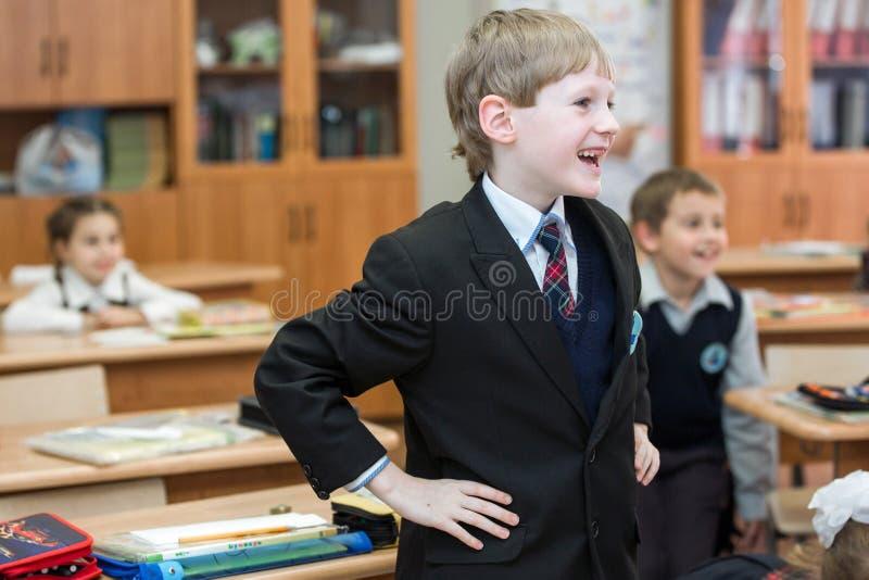 Lyckliga ungar i skolagrupp Barn har att göra övningar pojken lärer den huvudlästa skolalärare till fotografering för bildbyråer