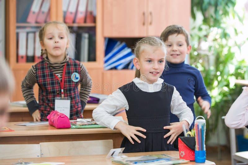 Lyckliga ungar i skolagrupp Barn har att göra övningar pojken lärer den huvudlästa skolalärare till arkivbild