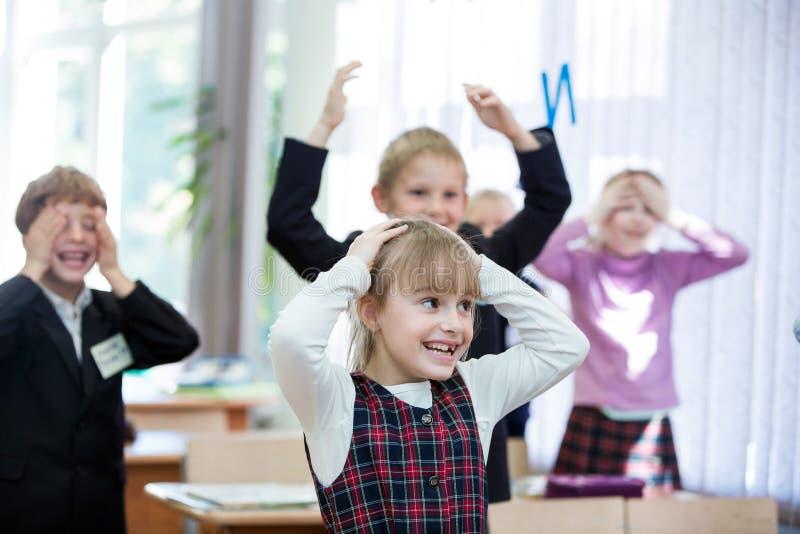 Lyckliga ungar i skolagrupp Barn har att göra övningar pojken lärer den huvudlästa skolalärare till royaltyfri foto