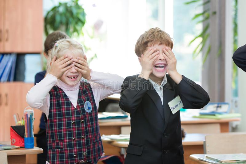 Lyckliga ungar i skolagrupp Barn har att göra övningar pojken lärer den huvudlästa skolalärare till arkivbilder