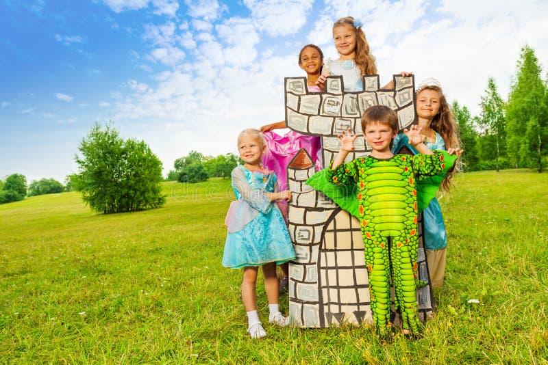 Lyckliga ungar i teater- dräkter spelar runt om torn arkivbilder