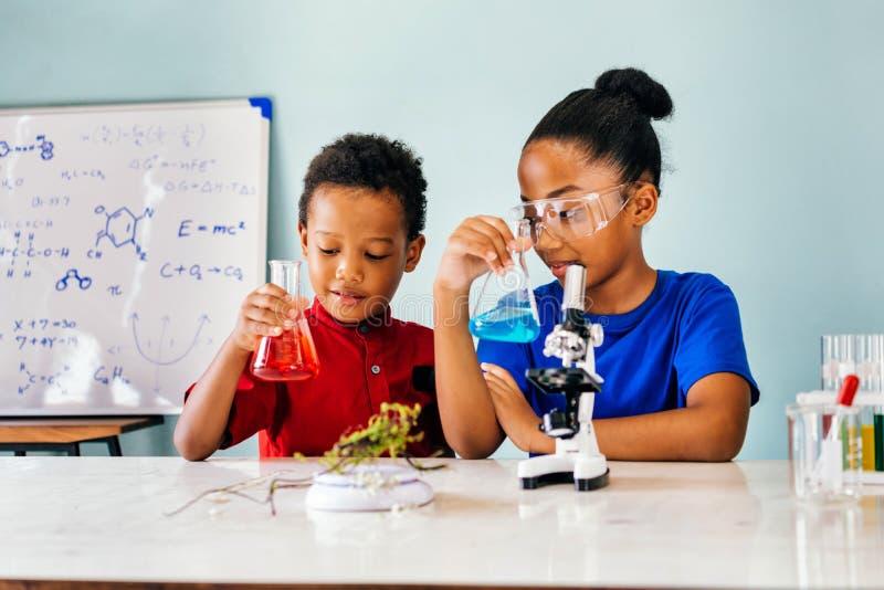 Lyckliga ungar med flaskor i skolakemilaboratorium royaltyfria bilder