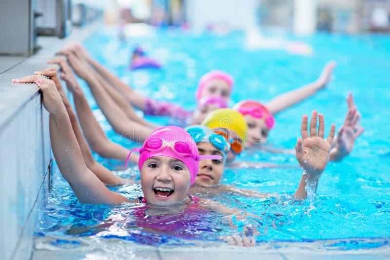 Lyckliga ungar på simbassängen Unga och lyckade simmare poserar fotografering för bildbyråer