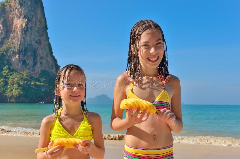 Lyckliga ungar på strandfamiljsemester, barn som äter tropisk frukt för ananas arkivbild