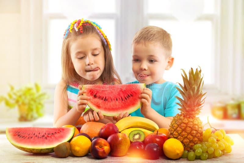 Lyckliga ungar som äter vattenmelon med frukter i kök arkivfoto