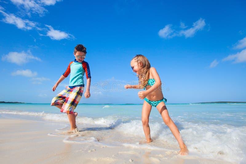 Lyckliga ungar som dansar på stranden arkivfoto