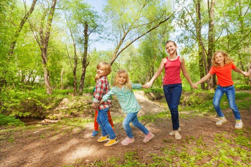 Lyckliga ungar som går i parkerainnehavhänderna arkivfoton