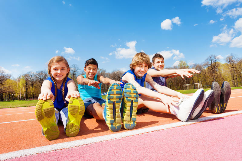 Lyckliga ungar som gör sträckning, övar på en stadion arkivfoto