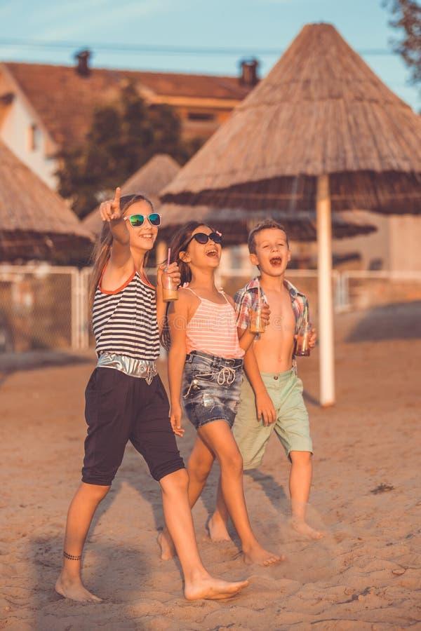 Lyckliga ungar som har gyckel p? stranden royaltyfria bilder