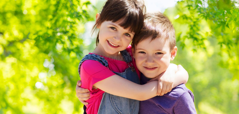 Lyckliga ungar som kramar över grön naturlig bakgrund royaltyfria foton