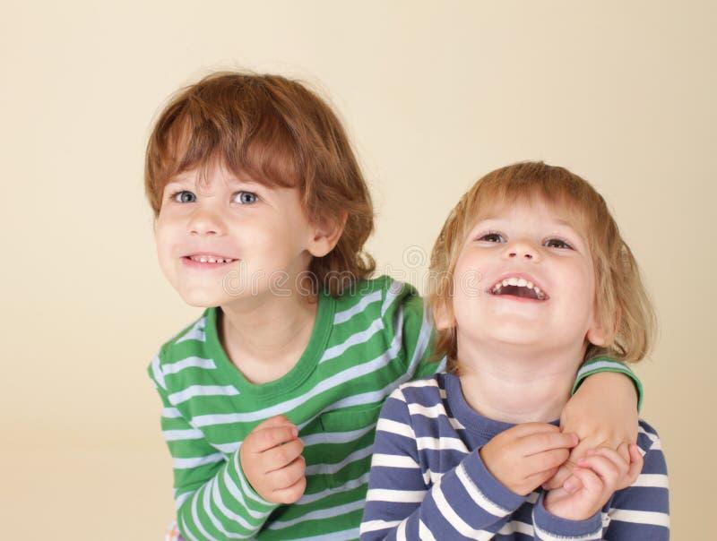 Lyckliga ungar som kramar och ler fotografering för bildbyråer