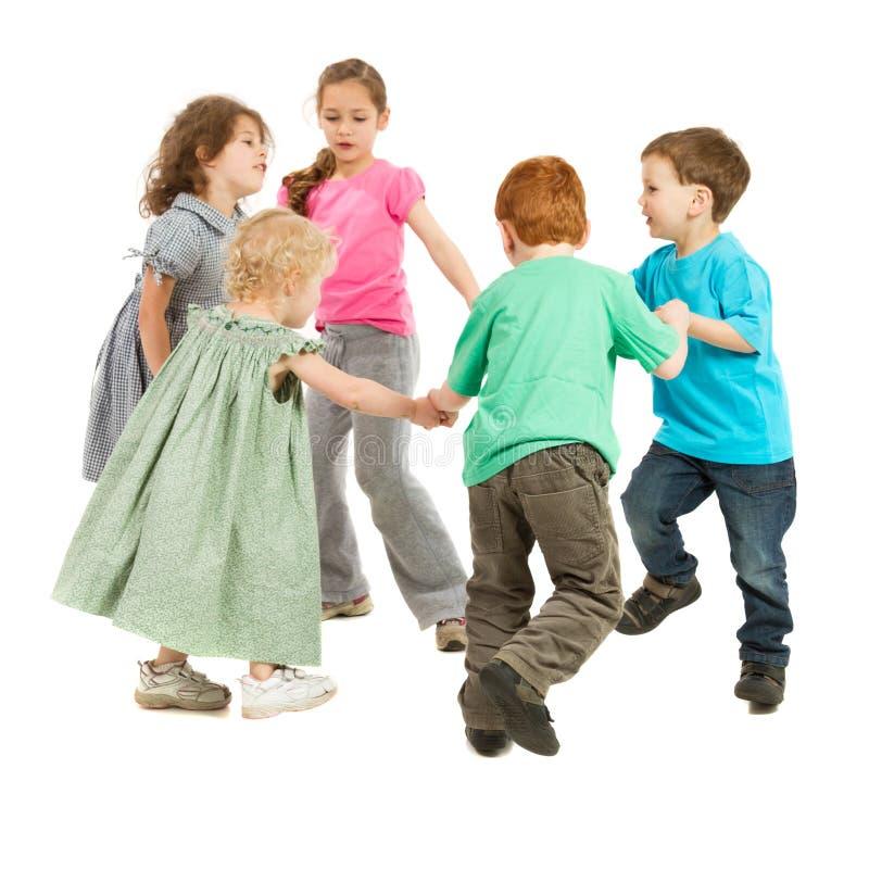 Lyckliga ungar som leker cirkelleken arkivbild