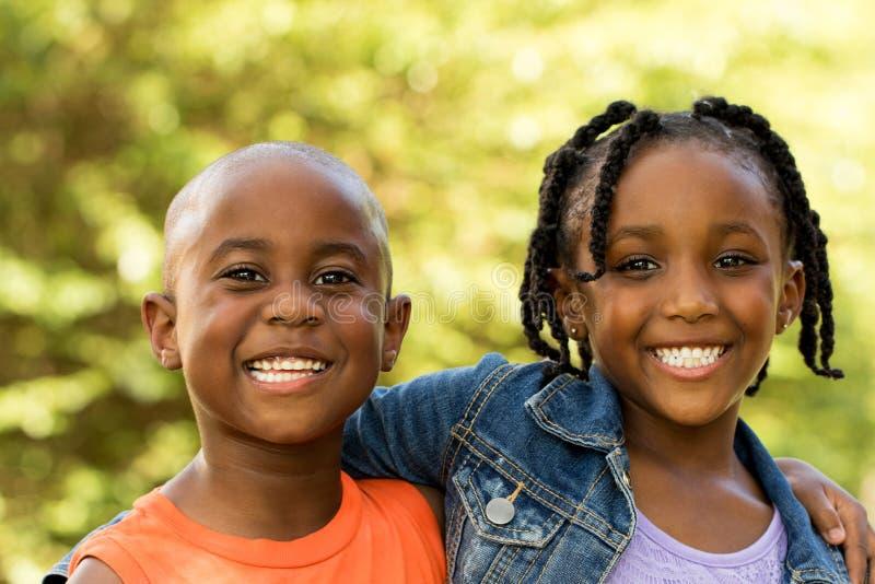 Lyckliga ungar som ler och ser kameran arkivbild