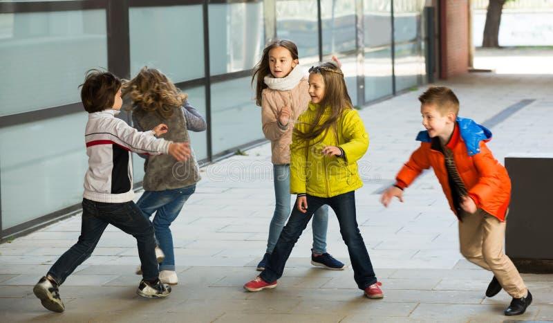 Lyckliga ungar som omkring kör, medan spela på etiketten arkivfoto