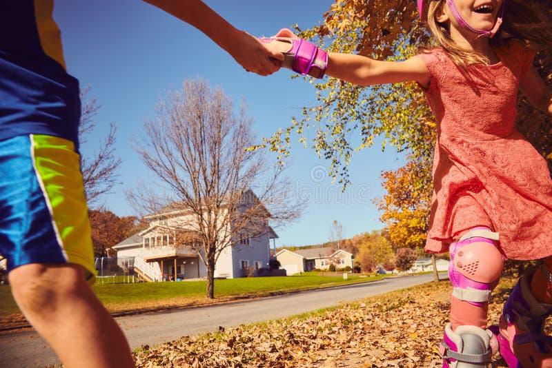 Lyckliga ungar som rymmer händer medan rollerskating fotografering för bildbyråer