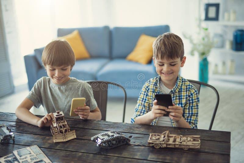 Lyckliga ungar som rymmer smartphones och tar foto av deras träkonstruktörer royaltyfri foto