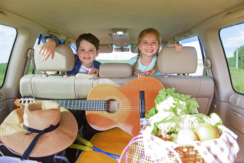 Lyckliga ungar som sitter i bil arkivfoto