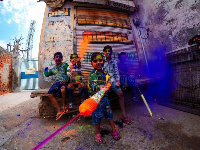 Lyckliga ungar som spelar holi i Indien royaltyfria foton