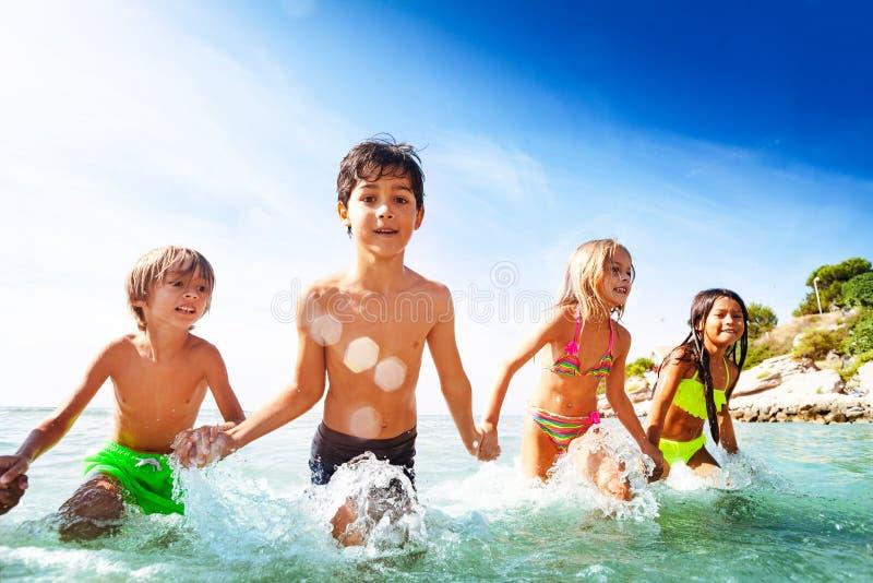 Lyckliga ungar som spelar i vatten under sommarsemester royaltyfri foto